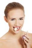 Όμορφη καυκάσια τόπλες γυναίκα με το ακατέργαστο σκόρδο στο στόμα. Στοκ Εικόνα