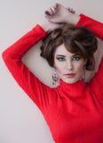 Όμορφη καφετής-μαλλιαρή γυναίκα σε ένα κόκκινο πουλόβερ με μια σύνθεση Στοκ εικόνα με δικαίωμα ελεύθερης χρήσης