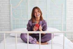 Όμορφη καφετής-μαλλιαρή θηλυκή συνεδρίαση στο κρεβάτι με ένα φλυτζάνι του coffe Στοκ φωτογραφία με δικαίωμα ελεύθερης χρήσης