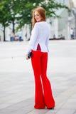 Όμορφη καφετής-μαλλιαρή νέα γυναίκα που φορά τα ενδύματα και το περπάτημα ο Στοκ Εικόνες