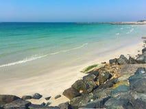 όμορφη κενή θερινή πετοσφαίριση παραλιών σφαιρών ανασκόπησης Δύσκολη παραλία με τις μαύρες πέτρες Άσπρο β Στοκ Εικόνα