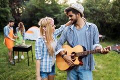 Όμορφη κιθάρα παιχνιδιού ατόμων στη φίλη του στη φύση Στοκ Φωτογραφία