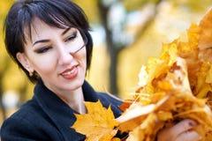 Όμορφη κινηματογράφηση σε πρώτο πλάνο προσώπου γυναικών με τη χούφτα των κίτρινων φύλλων το φθινόπωρο υπαίθριο, δέντρα στο υπόβαθ Στοκ Φωτογραφίες