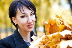 Όμορφη κινηματογράφηση σε πρώτο πλάνο προσώπου γυναικών με τη χούφτα των κίτρινων φύλλων το φθινόπωρο υπαίθριο, δέντρα στο υπόβαθ Στοκ Φωτογραφία