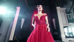 Όμορφη κομψή γυναίκα στο καταπληκτικό κόκκινο φόρεμα βραδιού που χορεύει στην εκλεκτής ποιότητας εσωτερική χαμηλή γωνία πολυτέλει φιλμ μικρού μήκους