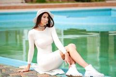 όμορφη κομψή γυναίκα φορε&m Προκλητικό brunette που βρίσκεται από την μπλε πισίνα υπαίθριο πορτρέτο μόδας Θέρετρο πολυτέλειας στοκ φωτογραφία