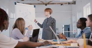 Όμορφη κομψή νέα βέβαια επιχειρηματίας που εξηγεί τα διαγράμματα στο f απόθεμα βίντεο