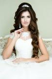 Όμορφη κομψή νύφη brunette με το γάμο makeup και hairstyle με τη συνεδρίαση κορωνών διαμαντιών στην εκλεκτής ποιότητας πολυθρόνα Στοκ εικόνες με δικαίωμα ελεύθερης χρήσης
