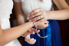 Όμορφη κομψή παράνυμφος που βάζει στο βραχιόλι της νύφης Στοκ φωτογραφία με δικαίωμα ελεύθερης χρήσης