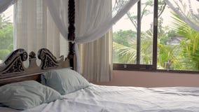 Όμορφη κρεβατοκάμαρα με ένα κρεβάτι τεσσάρων αφισών σε ένα ιδιωτικό ενοίκιο βιλών διακοπών πολυτέλειας στο τροπικό δάσος στην Ασί απόθεμα βίντεο