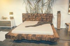 Όμορφη κρεβατοκάμαρα με το ξύλινο κρεβάτι στην έκθεση 2 επίπλων Στοκ Φωτογραφία