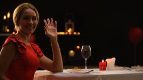 Όμορφη κυρία ευτυχής να δει το φίλο με τη δέσμη των τριαντάφυλλων, γεύμα στο εστιατόριο απόθεμα βίντεο