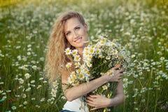 Όμορφη κυρία με τη χαριτωμένη κόρη camomile στον τομέα Στοκ Φωτογραφία