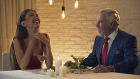 Όμορφη κυρία που γελά και που φλερτάρει με τον παλαιό πλούσιο άνθρωπο στο εστιατόριο, συνοδεία απόθεμα βίντεο