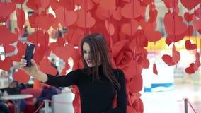 Όμορφη κυρία που θέτει και που παίρνει selfie στο υπόβαθρο των κόκκινων καρδιών Ευτυχής απόθεμα βίντεο