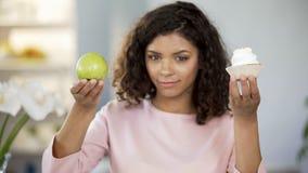 Όμορφη κυρία που παρουσιάζει το κέικ και μήλο, επιλογή τροφίμων, υγιής προτίμηση διατροφής στοκ εικόνα