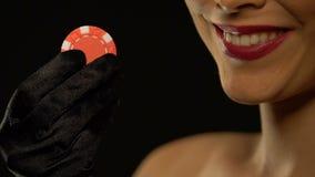 Όμορφη κυρία που παρουσιάζει τσιπ πόκερ στη κάμερα που απομονώνεται στο μαύρο υπόβαθρο απόθεμα βίντεο