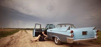 Όμορφη κυρία που στέκεται κοντά στο αναδρομικό αυτοκίνητο Στοκ Εικόνες