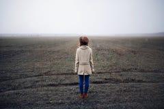 Όμορφη κυρία που στέκεται σε έναν τομέα στα τέλη του φθινοπώρου στοκ εικόνα
