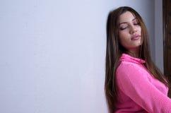 Όμορφη κυρία που φορά την πλέκοντας ρόδινη μπλούζα ενάντια στον τοίχο σπιτιών Στοκ Φωτογραφία