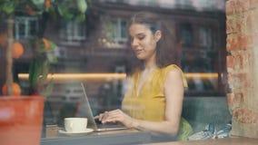 Όμορφη κυρία που χρησιμοποιεί το lap-top στη δακτυλογράφηση καφέδων που χαμογελά στον πίνακα πίσω από το παράθυρο γυαλιού απόθεμα βίντεο