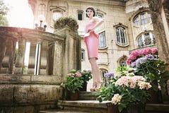Όμορφη κυρία στο ρόδινο φόρεμα, μπροστά από ένα παλαιό β Στοκ Εικόνες