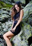 Όμορφη κυρία στο φόρεμα που κλίνει στους βράχους βουνών Στοκ εικόνα με δικαίωμα ελεύθερης χρήσης