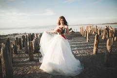 Όμορφη κυρία, τοποθέτηση νυφών σε ένα γαμήλιο φόρεμα κοντά στη θάλασσα στο ηλιοβασίλεμα Στοκ εικόνες με δικαίωμα ελεύθερης χρήσης