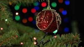Όμορφη κόκκινη σφαίρα με τη γιρλάντα στο χριστουγεννιάτικο δέντρο στη νύχτα Χριστουγέννων απόθεμα βίντεο