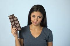Όμορφη λατινική γυναίκα με το φραγμό σοκολάτας που αισθάνεται ένοχη μετά από να δαγκώσει στο μπλε υπόβαθρο στη ζάχαρη και τη γλυκ Στοκ φωτογραφία με δικαίωμα ελεύθερης χρήσης
