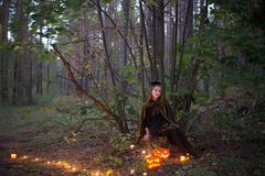 Όμορφη μάγισσα με μια κολοκύθα στο μαγικό δάσος στοκ εικόνες