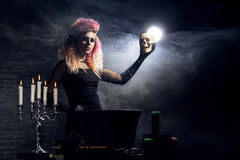 Όμορφη μάγισσα που κάνει witchcraft σε ένα καπνώές υπόβαθρο Εικόνα αποκριών Στοκ Φωτογραφίες