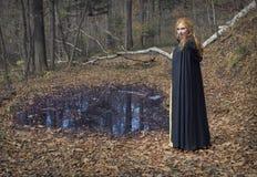 Όμορφη μάγισσα που φορά το μανδύα στο δάσος φθινοπώρου Στοκ Φωτογραφίες