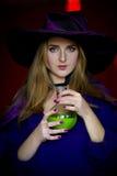 Όμορφη μάγισσα σε πορφυρές αποκριές με μια σκούπα Στοκ Φωτογραφίες