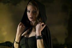 Όμορφη μάγισσα στο μαύρο μανδύα σε αποκριές στοκ εικόνες