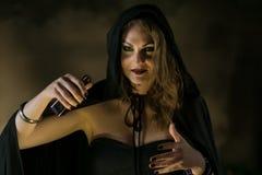 Όμορφη μάγισσα στο μαύρο μανδύα σε αποκριές στοκ εικόνα