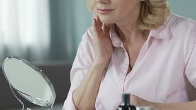 Όμορφη μέσης ηλικίας γυναίκα που κοιτάζει στον καθρέφτη και σχετικά με το δέρμα της, προσοχή φιλμ μικρού μήκους
