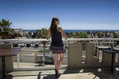 Όμορφη μέση ηλικίας γυναίκα που προσέχει τον μπλε ωκεανό από το μπαλκόνι με το βαθύ μπλε ουρανό Μακριά καφετιά τρίχα, κορυφή λουρ στοκ εικόνες