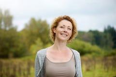 Όμορφη μέση ηλικίας γυναίκα που χαμογελά υπαίθρια Στοκ Εικόνες
