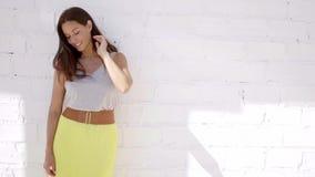 Όμορφη μέση ηλικίας τοποθέτηση brunette ενάντια στον τοίχο απόθεμα βίντεο