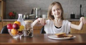 Όμορφη μαθήτρια με τη μακρυμάλλη συνεδρίαση στον πίνακα στην κουζίνα απόθεμα βίντεο