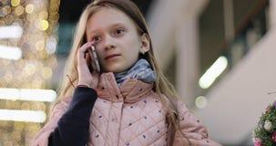 Όμορφη μαθήτρια που μιλά σε ένα τηλέφωνο κυττάρων φιλμ μικρού μήκους