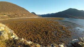 Όμορφη μακριά ακροθαλασσιά φθινοπώρου at low tide με τη φωτεινή ηλιοφάνεια, τη βαθιά θέα βουνού και το σαφή μπλε ουρανό φιλμ μικρού μήκους