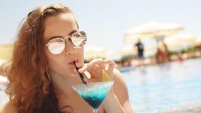 Όμορφη μακρυμάλλης χαλάρωση γυναικών κοντά στην πισίνα με το κοκτέιλ κίνηση αργή απόθεμα βίντεο