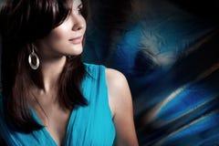 Όμορφη μακρυμάλλης γυναίκα σε ένα μπλε φόρεμα επάνω στοκ φωτογραφίες