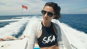 Όμορφη, μαυρισμένη γυναίκα στα μοντέρνα γυαλιά ηλίου που απολαμβάνει έναν περίπατο σε μια βάρκα στον ωκεανό Κυματίζοντας σημαίες  φιλμ μικρού μήκους