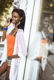 Όμορφη μαύρη γυναίκα που μιλά στο τηλέφωνο και το χαμόγελο Στοκ Φωτογραφία