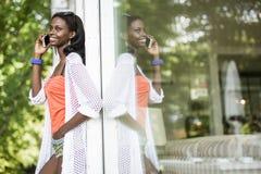 Όμορφη μαύρη γυναίκα που μιλά στο τηλέφωνο και το χαμόγελο Στοκ Εικόνα