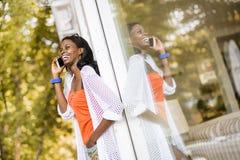 Όμορφη μαύρη γυναίκα που μιλά στο τηλέφωνο και το χαμόγελο Στοκ εικόνα με δικαίωμα ελεύθερης χρήσης