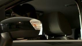 Όμορφη μαύρος-μαλλιαρή συνεδρίαση γυναικών στο αυτοκίνητο απόθεμα βίντεο